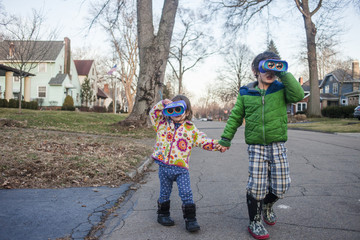 Siblings holding hands while looking through binoculars while playing on road