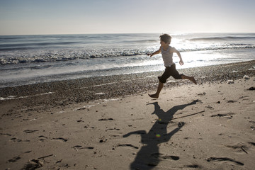 Playful boy running on sand at beach