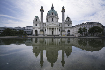 Karlskirche reflecting on pond against sky