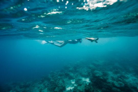 Snorkeling girl swimming with sea turtle