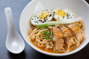 Close-up of ramen noodles with roasted chicken, egg, green onion and sesame seeds, selective focus
