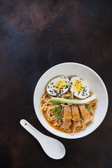 White bowl with chicken ramen noodles, flat-lay over dark brown metal background, vertical shot with copyspace
