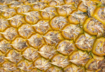 Ripe yellow pineapple skin texture closeup. Pineapple texture. Exotic fruit close-up. Ripe yellow fruit peel macro photo