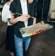 a man holds in his hand a palette with paints and a brush, and behind him they embrace. support
