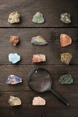 Overhead view of colorful gemstones with magnifying glass on wooden table
