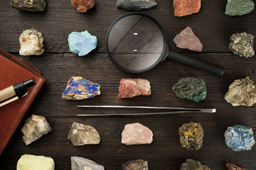 Overhead view of colorful gemstones with magnifying glass and tweezers on wooden table