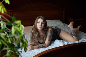 Plus size sexy model with tattoos lies on a large bed