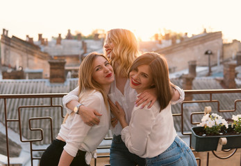 Girls Party. Beautiful Women Friendship on the balcony or roof At Bachelorette Party during sunset. They are hugging