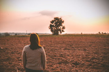 Portrait of lonely woman alone in a field. Vintage filter style.she heartbreak from love,sad girl concept on sunset vintage style