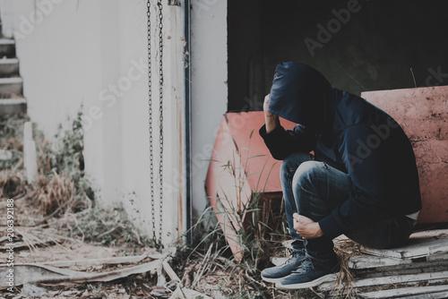 Portrait of asian man sad,drug addict man sitting on the floor