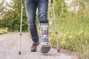 Mann läuft mit einer Orthese und Gehhilfen über einen Feldweg