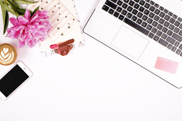 Top view of female worker desktop with laptop, flowers and different office supplies items. Feminine creative design workspace.