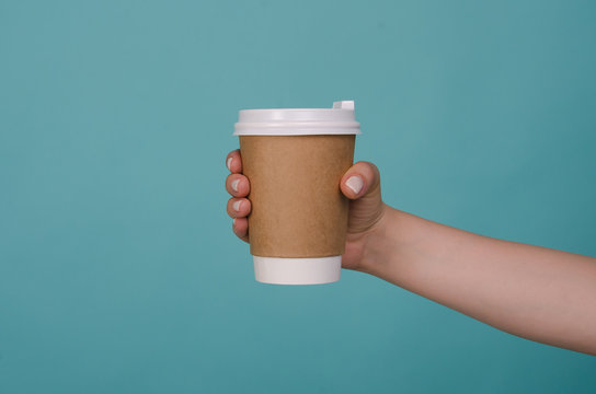 Coffee cup in woman hand isolated on blue background. Female hand with paper cup. Mockup of female hand holding a coffee paper cup. Copy space