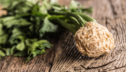 Fresh celery root with leaf on rustic oak table