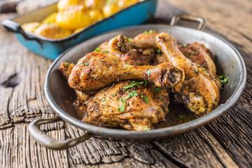 Roasted chicken legs in pan on rustic oak table