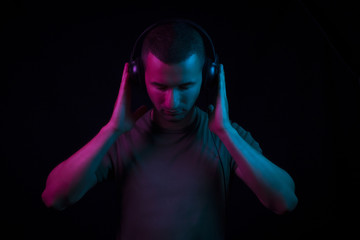 A dj holding his head set on black background under magenta and blue gel lighting