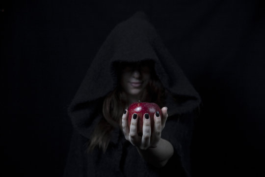 Snow white's red apple in the hand of a black witch with black painted nails
