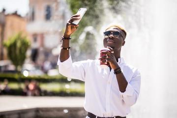 Afro american man take selfie on phone near fountain or make vidio streem live translation on summer streets