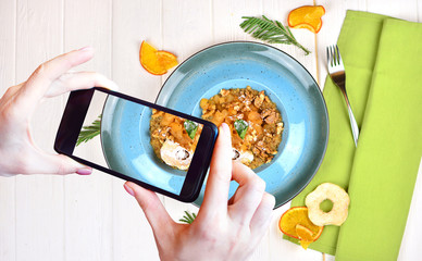 Girl makes food photo on phone camera of her breakfast. Tasty fitness breakfast with a design. Morning healthy food background.