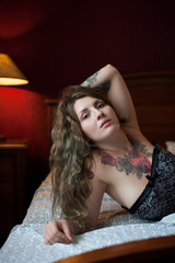 Plus size Sexy model with gothic tattoos lies on a bed