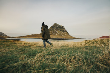 Young caucasian man walking with Kirkjufell Mountain