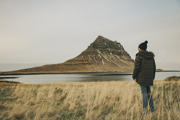 Young caucasian man standing and staring at  Kirkjufell Mountain