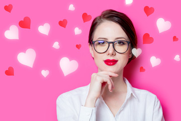 Beautiful redhead businesswoman in white shirt with abstract hearts on pink background