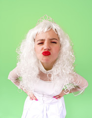 Photo of upset princess with long white hair and red lips looks at camera with anger isolated over light green background