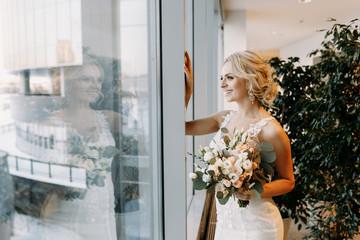 Beautiful bride in a white dress stands near the window in a hypermarket ,blonde
