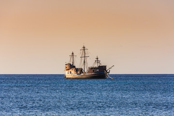 Old wooden sailboat at sunset in the Caribbean sea. Beautiful sky color at twilight. Blue water. Side view.