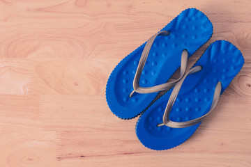 Blue sandal shoes on wooden table, top view