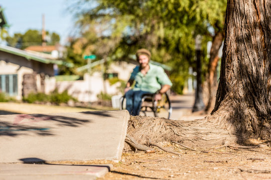 Deep Focus Man in Wheelchair Faces Sidewalk Obstacle