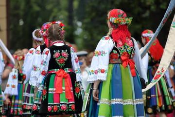 Obraz Dziewczyny ubrane w odświętne ludowe stroje łowickie idą w tradycyjnej procesji podczas święta Bożego Ciała, widok z tyłu, kolorowe stroje, słonecznie - fototapety do salonu