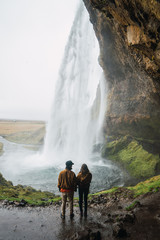 Romantic people near amazing waterfall