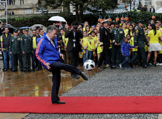 Colombia's President Juan Manuel Santos kicks a ball during a ceremony handing the Colombian flag to the national soccer team's captain at the Presidential Palace in Bogota