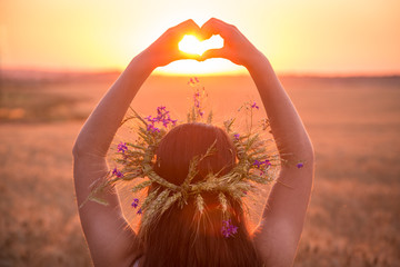 girl on wheat field making heart symbol at sunset
