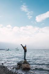 Happy girl balancing on rock in sea