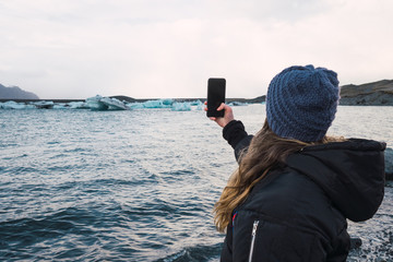 Woman taking photo on cold beach
