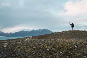Woman with camera standing on mountains