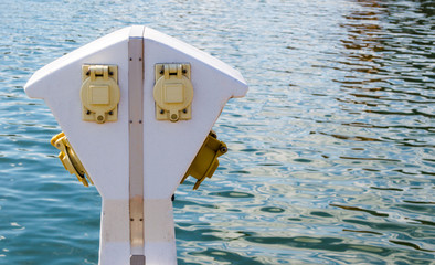 a white and yellow nautical power pedestal on the waterfront at Baltimore's Inner Harbor with copy space