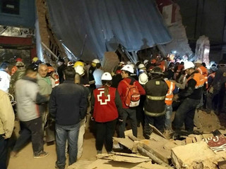 Rescue workers gather at the site where a cinema has collapsed in Tucuman