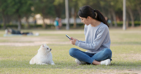Woman taking photo on her dog at outdoor park
