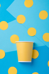 Yellow paper cup for a party on a blue background