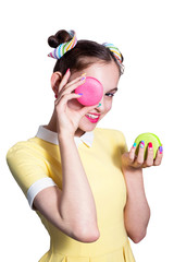 A young beautiful girl is holding a multicolored macaroons in her hands and closes one eye with a macaroon. Hands with bright manicure, funny hair. Isolated on white background.