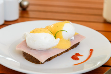 Egg benedict on white dish on breakfast - Poached egg on ham slices and a piece of bread