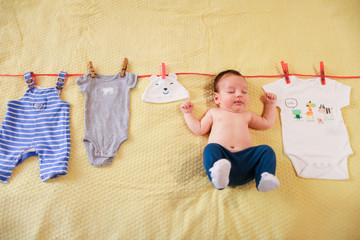 Little cute baby hanging with clothes on rope. Concept of funny photo session for babies.