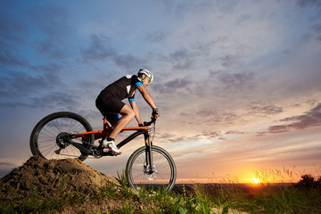 View of energetic and active man in helmet and sportswear riding orange bike in the evening. Sporty and energetic athlete sitting and rolling down hill at sunset. Recreative fresh air activities.