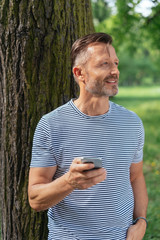 man leaning on a tree trunk holding his mobile phone