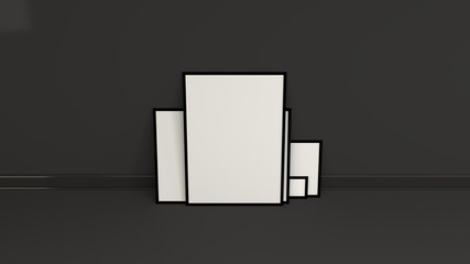 Blank white posters in black frames standing on the floor