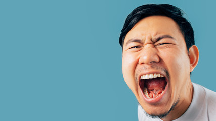 Face of Asian man shout and scream on isolated background.